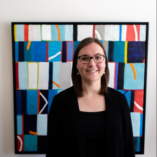 Picture of Dr. Lieke van Heumen, a white woman with dark brown hair and dark eyes and glasses. She is standing in front of a colorful modern painting.
